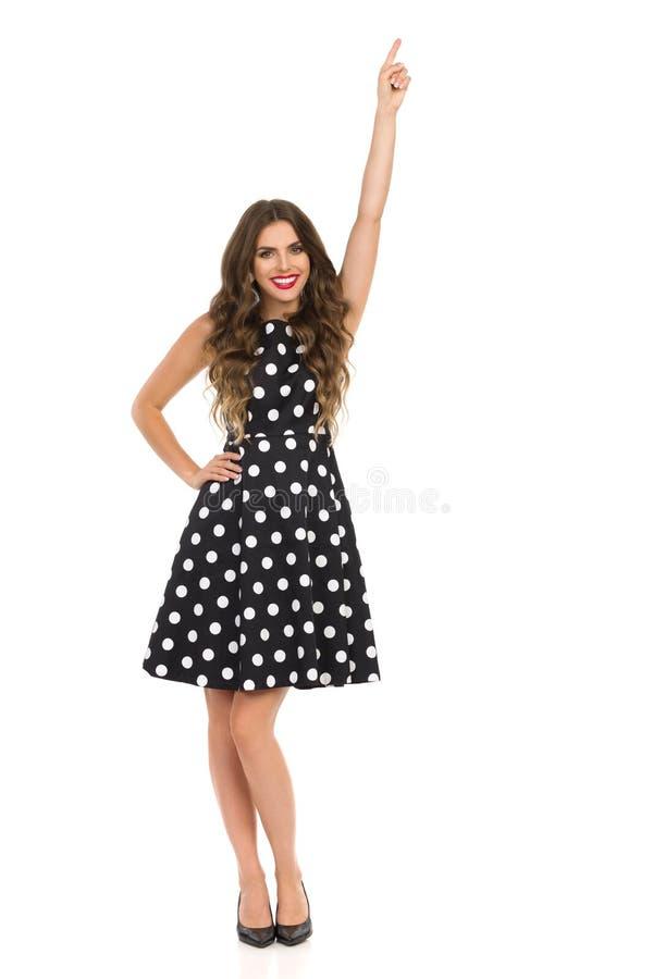 Mooie Jonge Vrouw in Zwarte Cocktailkleding in en Polka Dots And High Heels Is die benadrukken glimlachen stock foto