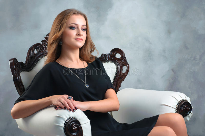 Mooie jonge vrouw in zwarte kleding met juwelenzitting in royalty-vrije stock afbeelding