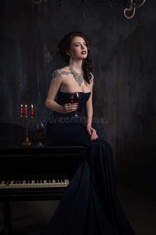 Mooie jonge vrouw in zwarte kleding naast een piano met kandelaberskaarsen en wijn, donkere dramatische atmosfeer van het kasteel stock foto