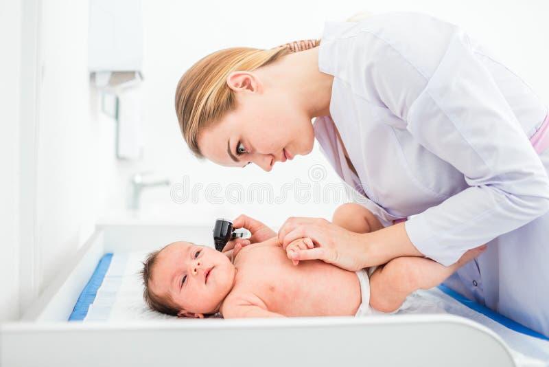Mooie jonge vrouwelijke blonde arts die weinig baby met oorspeculum onderzoeken in kliniek Het Concept van de babygezondheid stock fotografie