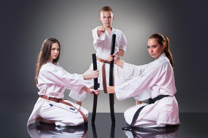 Mooie jonge vrouwelijke karatespelers die met zwaard op de grijze achtergrond stellen Mannelijke vechter op de achtergrond stock foto