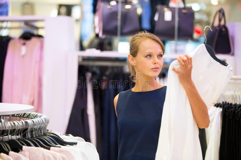 Mooie jonge vrouwelijke klant in een kledingsopslag stock foto