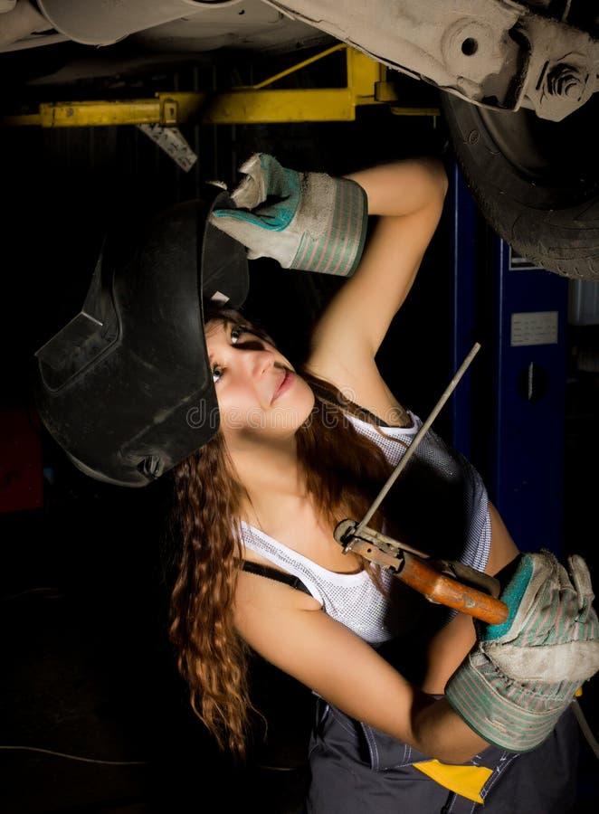 Mooie jonge vrouwelijke mechanische het inspecteren auto in autoreparatiewerkplaats De meisjeslasser is bereid om delen te verbin royalty-vrije stock foto's