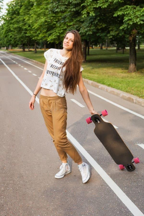 Mooie jonge vrouwelijke student met lang haar die en een longboard op de weg in het park bevinden zich houden skateboarding outdo stock foto