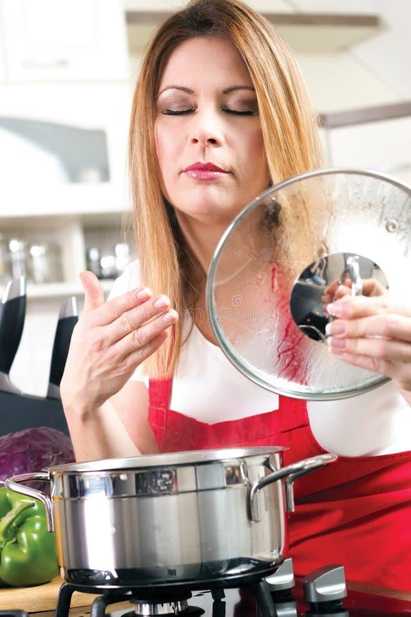 Mooie jonge vrouwen die en het voedsel in kitche koken testen stock foto
