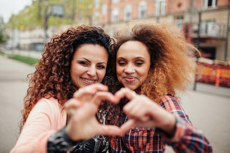 Mooie jonge vrouwen die hartvorm maken stock foto
