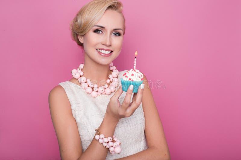 Mooie jonge vrouwen die kleine cake met kleurrijke kaars houden Verjaardag, vakantie royalty-vrije stock afbeeldingen