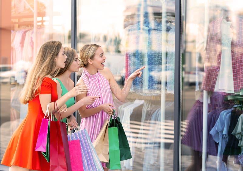 Mooie jonge vrouwen die met het winkelen zakken showcase van opslag bekijken stock fotografie