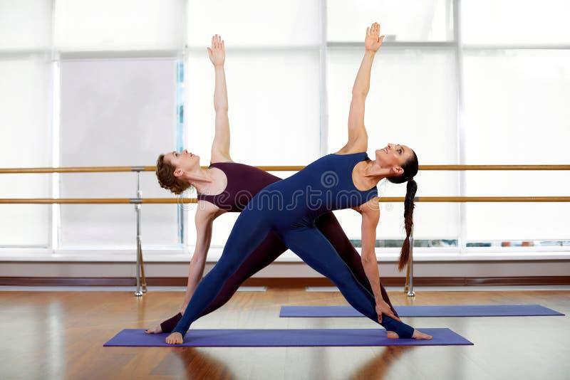Mooie jonge vrouwen die in paren gerangschikte uitrekkende oefeningen doen De meisjes in de gymnastiek doen geschiktheidsoefening stock foto's