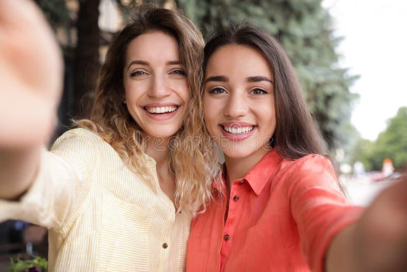 Mooie jonge vrouwen die selfie op zonnige dag nemen stock afbeeldingen