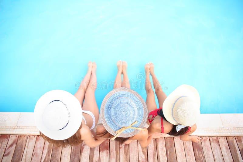 Mooie jonge vrouwen in zwemmende kostuums dichtbij pool op de zomerdag stock fotografie