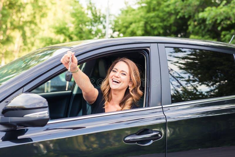 Mooie jonge vrouwenbestuurder die autosleutels ter beschikking tonen stock foto's