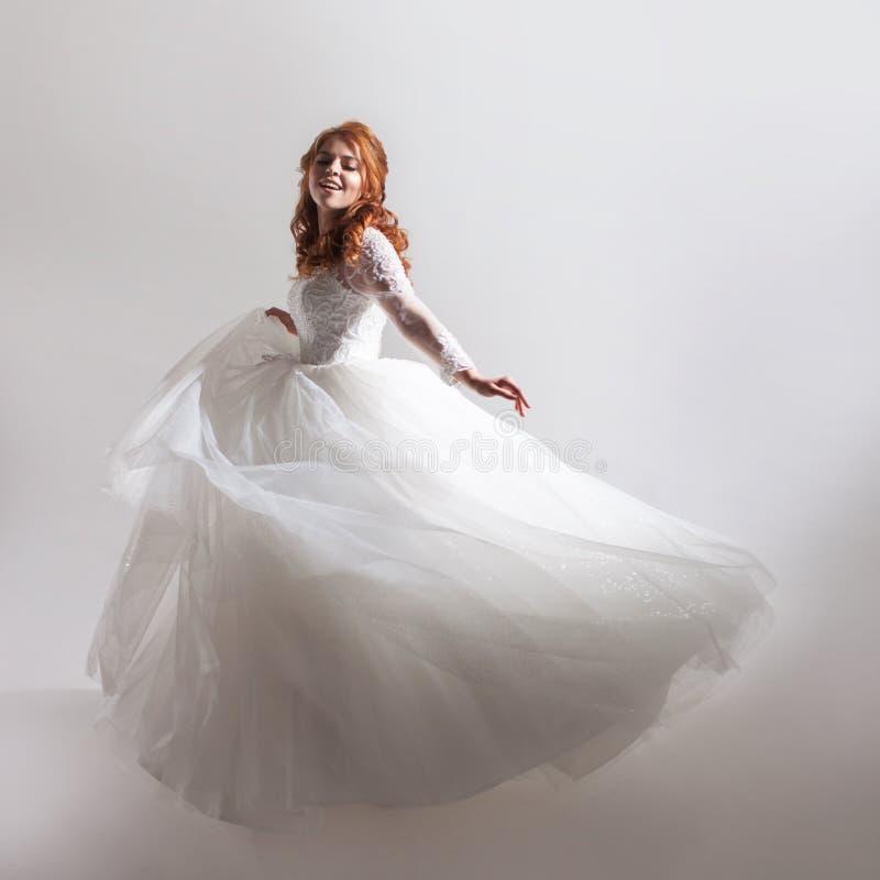 Mooie jonge vrouwenbruid in een overvloedige huwelijkskleding Lichte achtergrond royalty-vrije stock fotografie