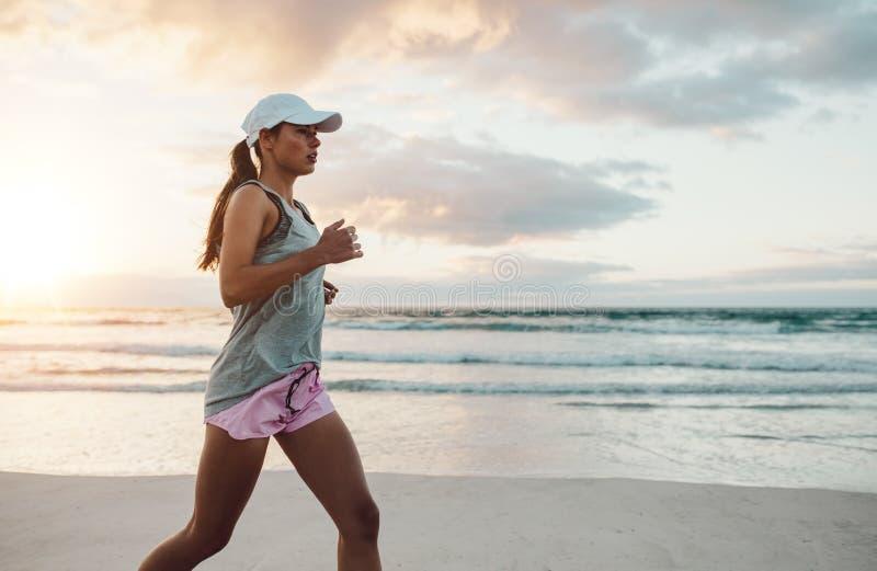 Mooie jonge vrouwenjogging op strand royalty-vrije stock foto