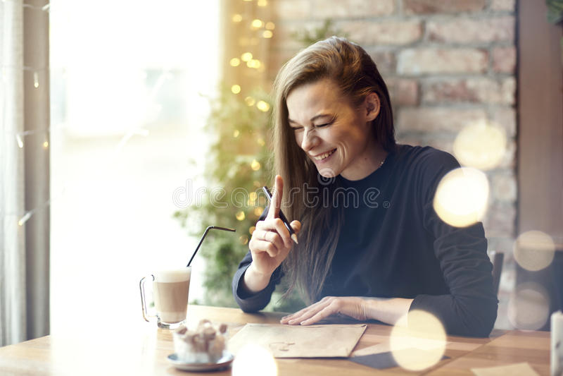 Mooie jonge vrouwenlach het drinken koffie in koffierestaurant, portret van lachende gelukkige dame dichtbij venster Roepingsvaka royalty-vrije stock afbeeldingen
