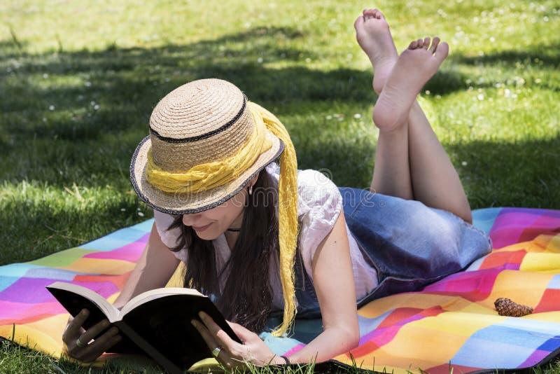 Mooie jonge vrouwenlezing in het park royalty-vrije stock afbeeldingen