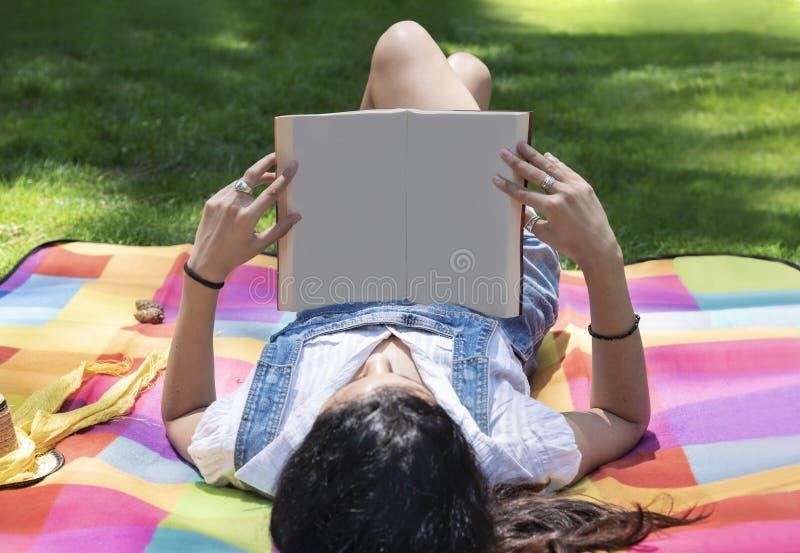 Mooie jonge vrouwenlezing in het park royalty-vrije stock foto's