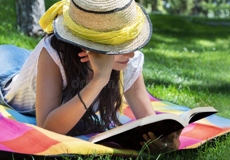 Mooie jonge vrouwenlezing in het park royalty-vrije stock afbeelding
