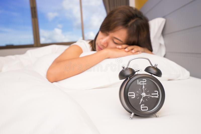 Mooie jonge vrouwenslaap en het glimlachen terwijl het liggen in bed comfortabel en gelukzalig op de achtergrond van wekker stock afbeeldingen