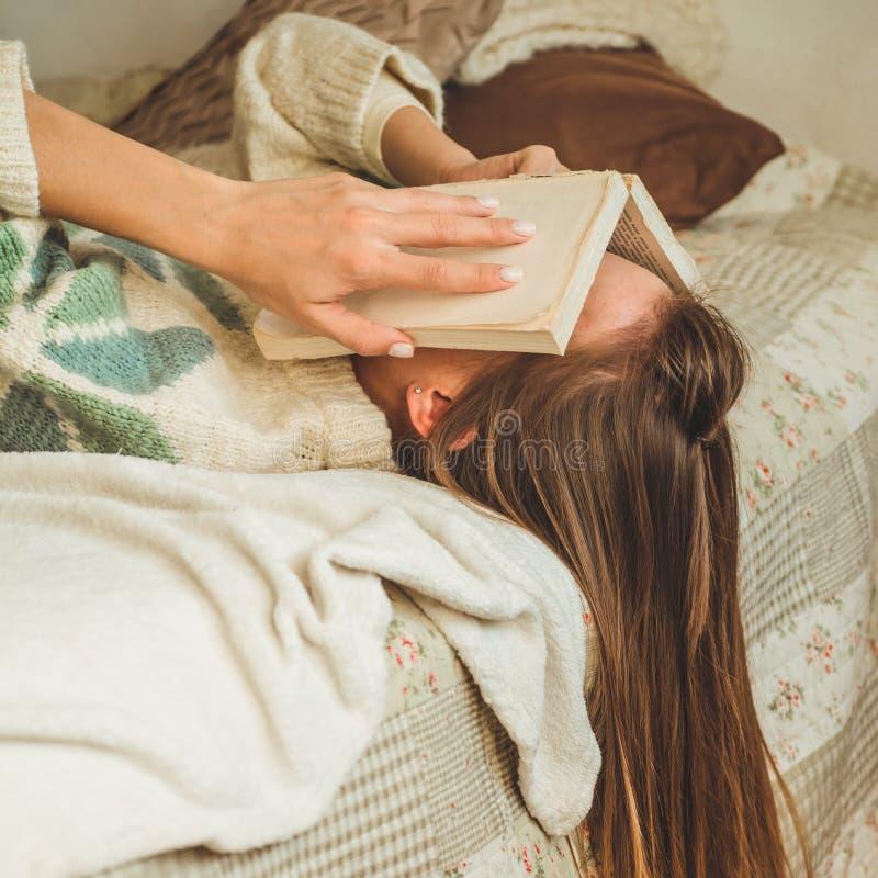 Mooie jonge vrouwenslaap op bed met boek die haar gezicht behandelen omdat lezingsboek met het voorbereiden van examen van univer stock fotografie