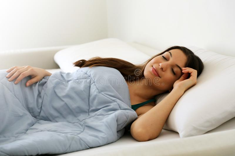 Mooie jonge vrouwenslaap terwijl gelukzalig het liggen in bed comfortabel en royalty-vrije stock foto