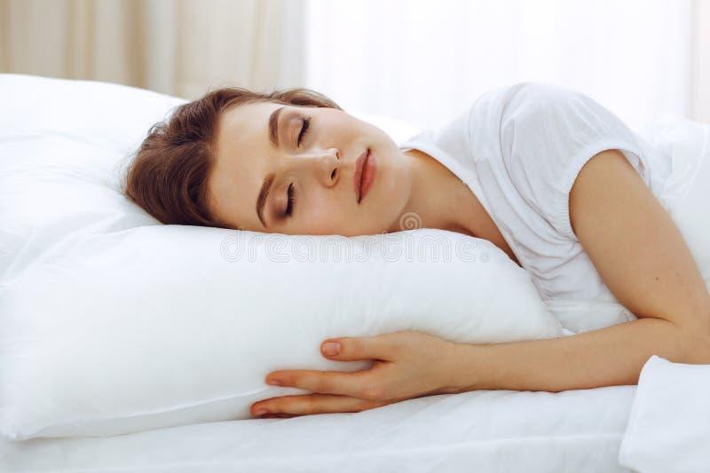 Mooie jonge vrouwenslaap terwijl het liggen in haar bed Concept prettig en rust herstel voor het actieve leven stock foto