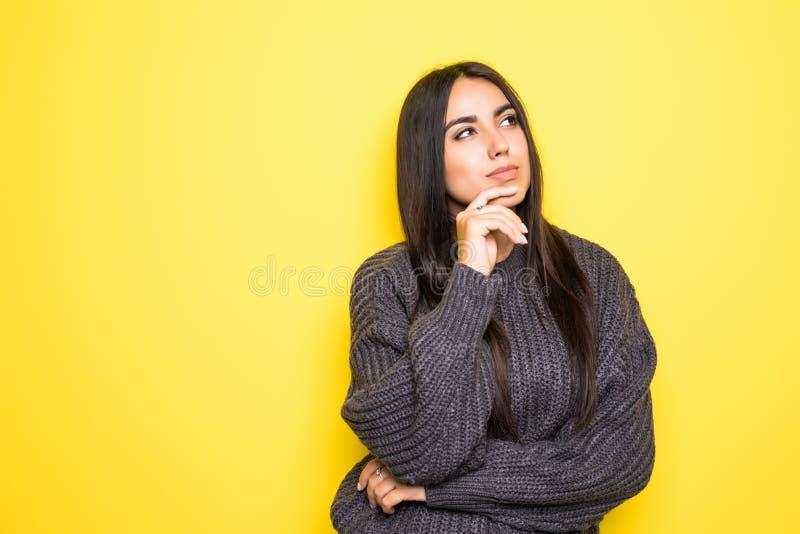 Mooie jonge vrouwensweater die, en camera op gele achtergrond bekijken glimlachen stock foto's