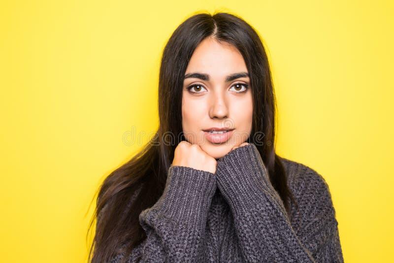 Mooie jonge vrouwensweater die, en camera op gele achtergrond bekijken glimlachen royalty-vrije stock afbeeldingen