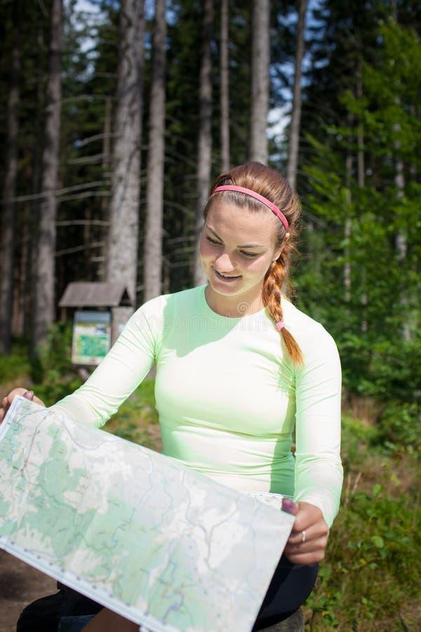 Mooie jonge vrouwentoerist die kaart bekijken stock afbeeldingen
