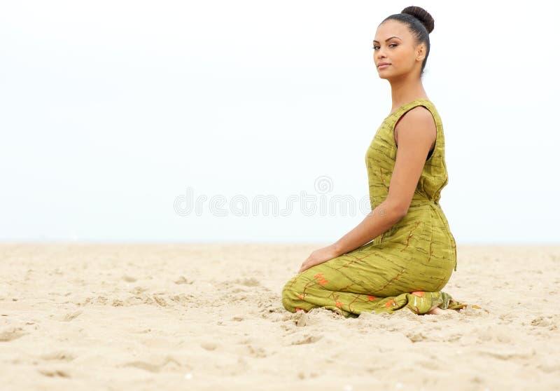 Mooie jonge vrouwenzitting alleen op zand bij het strand royalty-vrije stock foto's