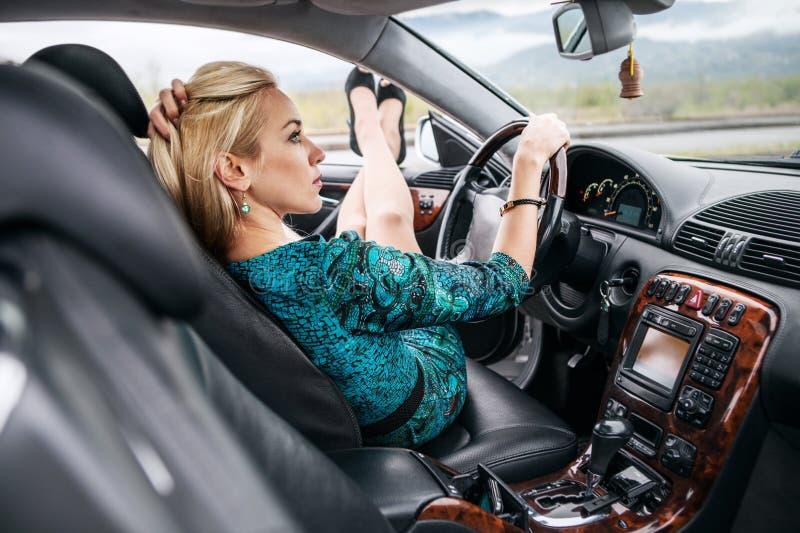Mooie jonge vrouwenzitting in auto stock foto
