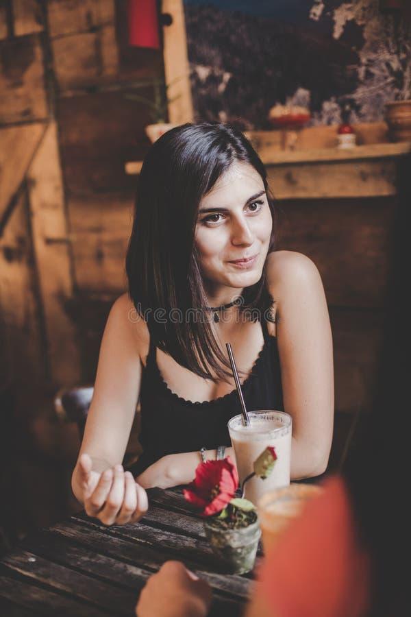 Mooie jonge vrouwenzitting bij koffie, drinkend smoothie en hebbend pret met haar vriend stock fotografie