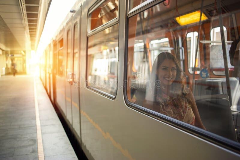 Mooie jonge vrouwenzitting in een metro stock fotografie