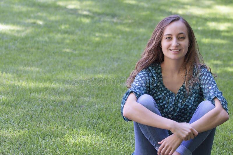 Mooie, jonge vrouwenzitting met de benen over elkaar op het gras royalty-vrije stock afbeelding