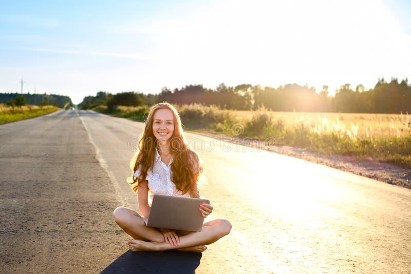 Mooie jonge vrouwenzitting met laptop en het glimlachen op de weg die voorbij de horizon bij zonsondergang gaan stock afbeeldingen