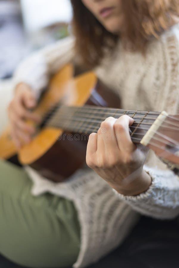 Mooie jonge vrouwenzitting op bank het spelen gitaar royalty-vrije stock afbeelding