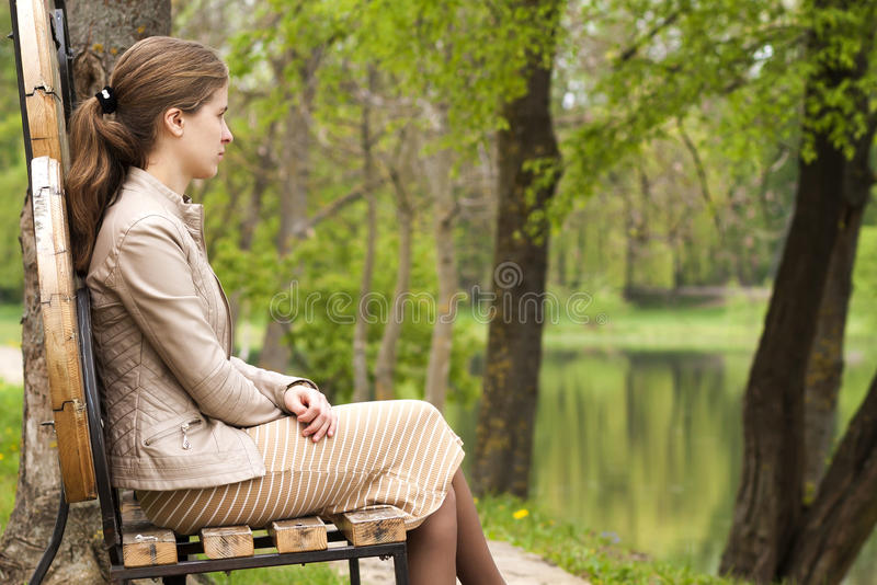 Mooie jonge vrouwenzitting op bank in park het vooruitzien stock foto's