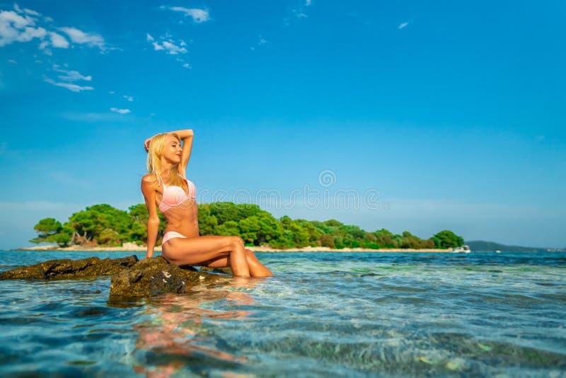 Mooie jonge vrouwenzitting op de rotsen bij Blauw lagunestrand in Kroatië royalty-vrije stock fotografie