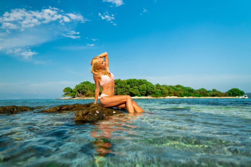 Mooie jonge vrouwenzitting op de rotsen bij Blauw lagunestrand in Kroatië stock foto's