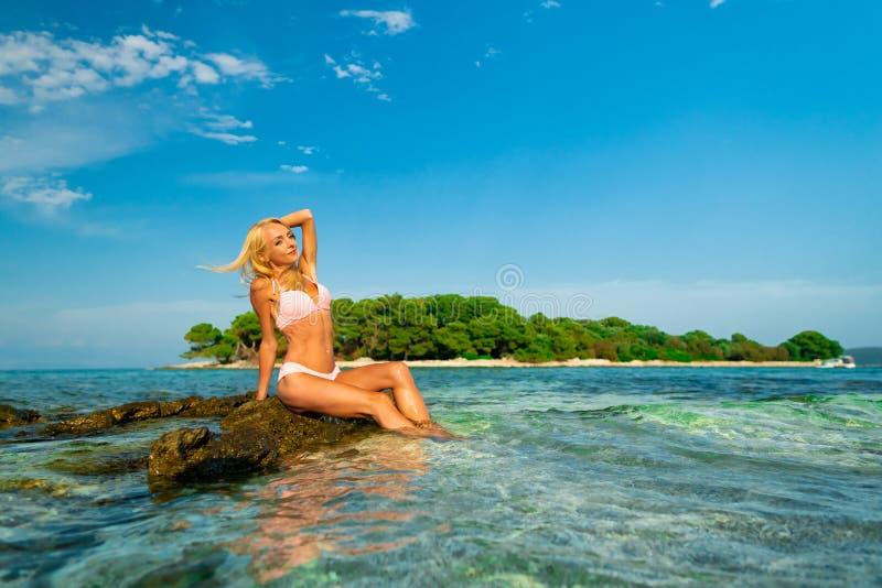 Mooie jonge vrouwenzitting op de rotsen bij Blauw lagunestrand in Kroatië royalty-vrije stock foto's