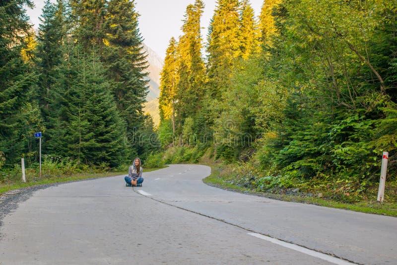 Mooie jonge vrouwenzitting op de weg en vooruit het kijken Rond de boskronkelweg royalty-vrije stock foto