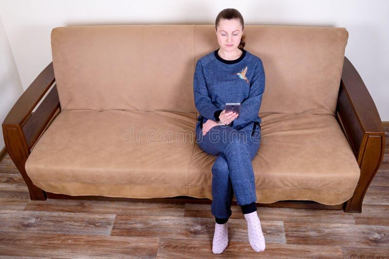 Mooie jonge vrouwenzitting op een bank, het gebruiken van een smartphone en het texting Thuis het ontspannen op de laag stock afbeeldingen