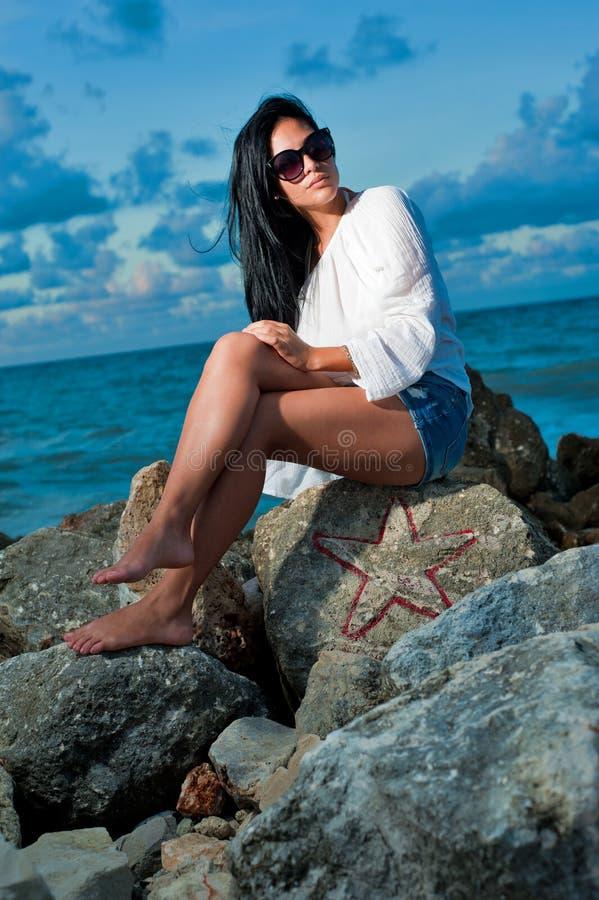 Mooie jonge vrouwenzitting op een rots door de oceaan royalty-vrije stock foto's