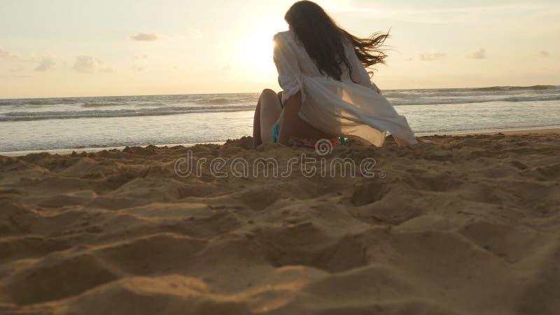 Mooie jonge vrouwenzitting op gouden zand op overzees strand tijdens zonsondergang en vraag aan zich Meisje het ontspannen op oce stock foto