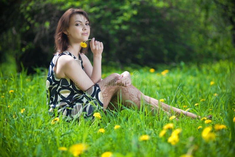 Mooie jonge vrouwenzitting op het gras stock foto