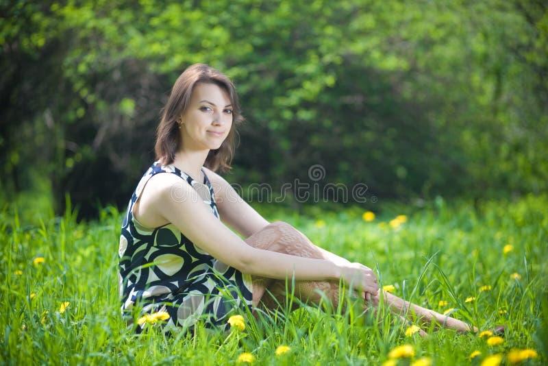Mooie jonge vrouwenzitting op het gras stock foto's