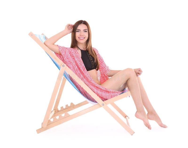 Mooie jonge vrouwenzitting op ligstoel stock foto's