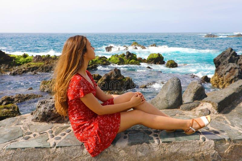 Mooie jonge vrouwenzitting op muur die van wind op haar gezicht met overweldigend zeegezicht in Puerto de la Cruz, Tenerife genie stock afbeeldingen