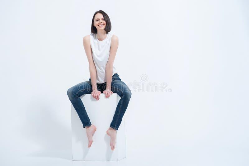 Mooie jonge vrouwenzitting op witte kubus in studio royalty-vrije stock foto's