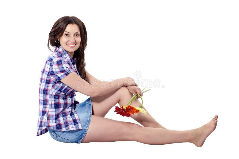 Mooie jonge vrouwenzitting in profiel met gerberas stock fotografie